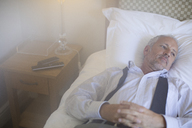 Businessman relaxing on bed in hotel room - CAIF16600
