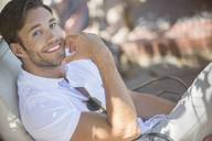 Smiling man relaxing outdoors - CAIF16603