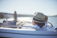 Older man relaxing in boat on water - CAIF16660
