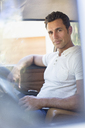 Man driving car on sunny day - CAIF16756