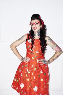 Portrait of tattooed woman wearing patterned red dress - ABIF00135