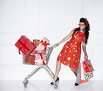 Tattooed woman with shopping bags and shopping cart full of gifts - ABIF00138