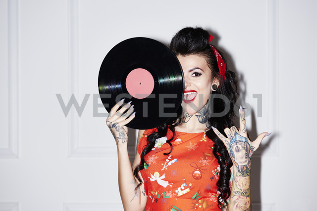 Portrait of tattooed woman with record showing Rock And Roll Sign - ABIF00141