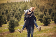 Man piggybacking woman while walking in pine tree farm - CAVF08330