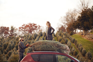 Man holding pine tree in net while looking at woman standing on car - CAVF08348