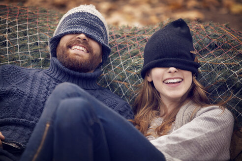 Playful couple wearing knit hat while leaning on Christmas tree in net - CAVF08357