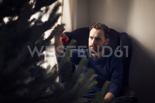 High angle view of man holding Christmas ornament - CAVF08360