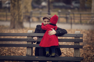 Father embracing baby girl standing on bench - CAVF08369