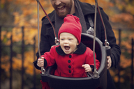 Father pushing baby girl on swing in park - CAVF08372