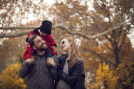 Baby playing with father's hair while sitting on shoulder - CAVF08375