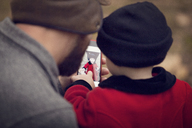 High angle view of father and baby girl looking at photograph in smart phone - CAVF08378