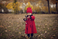 Full length of cute baby using mobile phone while standing on field - CAVF08384