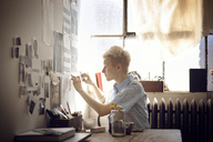 Woman sticking photographs on wall at home - CAVF08405