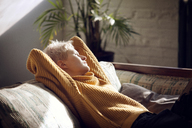 Woman looking away while relaxing on sofa at home - CAVF08432