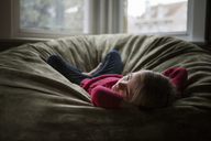Girl looking away while lying on bean bag at home - CAVF08465