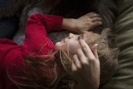 Overhead view of girl lying with mother on bean bag - CAVF08468