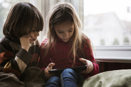 Siblings using tablet computer while sitting on bean bag at home - CAVF08471