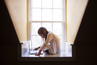 Girl using laptop computer while sitting by window at home - CAVF08477