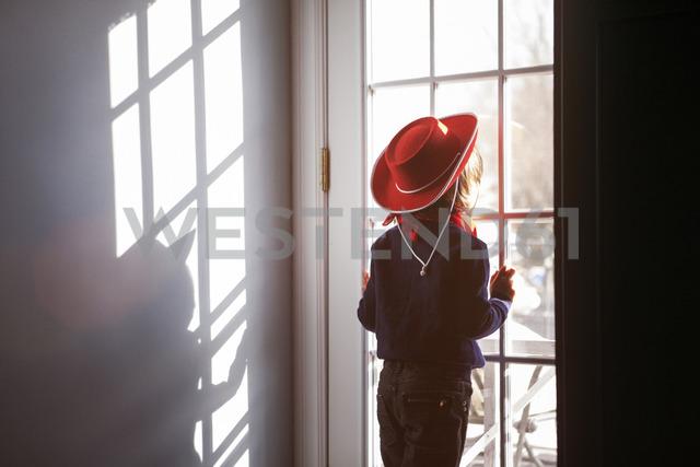 Rear view of boy in hat looking through window - CAVF08483