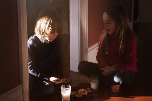 Siblings having breakfast while sitting on floor at home - CAVF08486