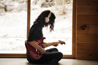 Side view of teenage girl playing guitar while sitting on floor at home - CAVF08522