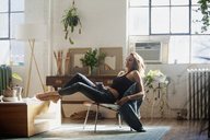 Happy woman sitting on chair at home - CAVF08573
