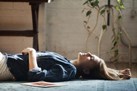 Side view of woman lying on floor at home - CAVF08585