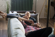 High angle view of couple relaxing on sofa at home - CAVF08588