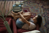 High angle view of woman relaxing on arm chairs at home - CAVF08651