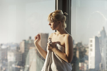 Woman wrapped in towel looking through window while standing at home - CAVF08687