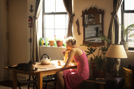 Side view of woman sitting by table at home - CAVF08708