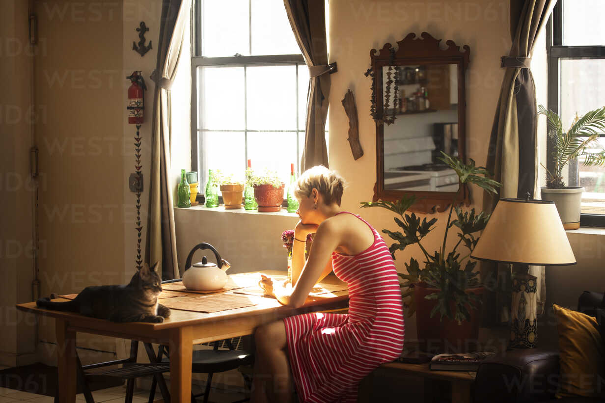 Side view of woman sitting by table at home - CAVF08708 - Cavan Images/Westend61