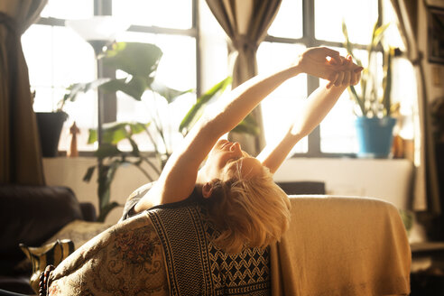 Woman stretching while leaning on sofa - CAVF08711