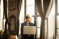 Woman with laptop computer sitting on window sill at home - CAVF08714