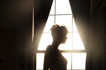 Side view of woman standing against window at home - CAVF08717