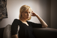 Thoughtful woman with hand in hair sitting on sofa at home - CAVF08720
