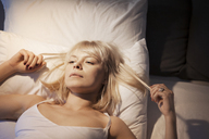 High angle view of woman lying on bed at home - CAVF08732