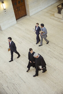 Judges and lawyer walking through courthouse - CAIF16845