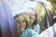 Happy mother and daughter looking out car window - CAIF16905