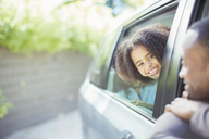 Father and daughter leaning out car windows - CAIF16923