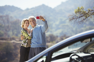 Senior couple taking self-portrait with cell phone outside car - CAIF16926