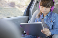 Girl with headphones using digital tablet in back seat of car - CAIF16956