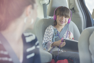 Mother turning and smiling at daughter with headphones and digital tablet in back seat of car - CAIF16962