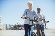 Portrait of senior couple with bicycles on beach boardwalk - CAIF16989