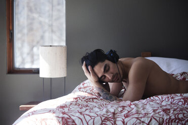 Shirtless man with hand in hair listening music while lying in bed - CAVF08765