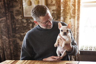 Man looking at French bulldog while sitting by table at home - CAVF08792