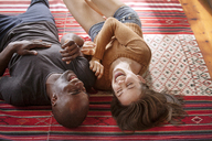 High angle view of cheerful couple lying on mat at home - CAVF08810