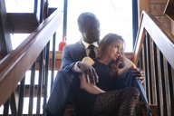 Low angle view of couple sitting on stairs - CAVF08822