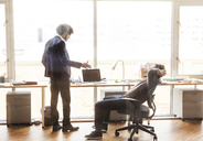Businessman explaining while coworker relaxing on chair at office - CAVF08930