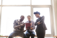 Businessmen and businesswoman looking at tablet while sitting at office - CAVF08936